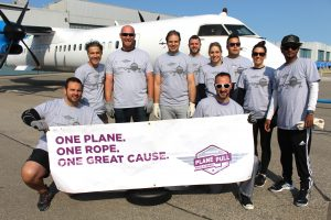 Team posing in front of plane