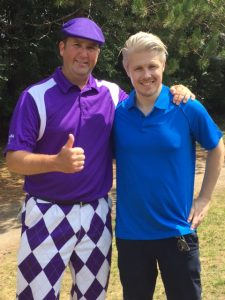 Community event organizer posing at golf tournament with Dr. David Taylor