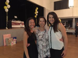 Mother and two daughters smiling at camera