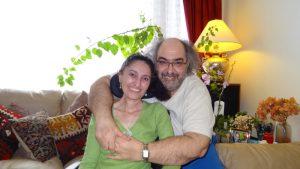 Zehra and Sinan hugging and smiling at the camera